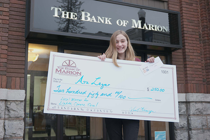 Ava Lazar standing in fron of the Bank of Marion with a big check.